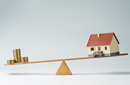 mortgage rates: Model house and money coins balancing on a seesaw