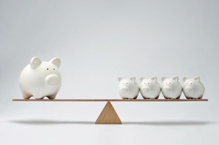 inflation basket: Small piggy banks and large piggy bank balancing on a seesaw