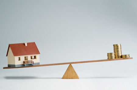 subprime mortgage crisis: Model house and money coins balancing on a seesaw