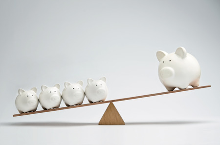 Small piggy banks and large piggy bank balancing on a seesaw