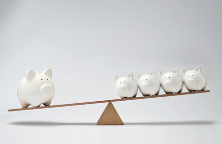 Small piggy banks and large piggy bank balancing on a seesaw photo