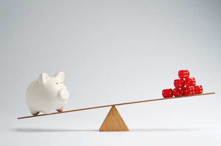 savings risk: Dice stack and piggy bank balancing on a seesaw