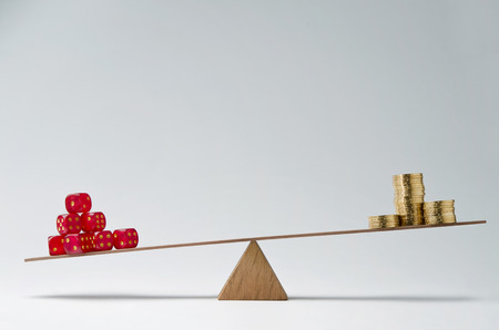 savings risk: Dice stack and money coins balancing on a seesaw