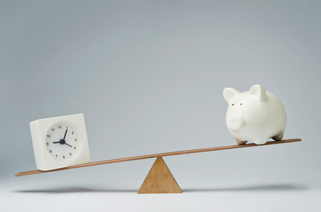 savings problems: Clock and piggy bank balancing on a seesaw