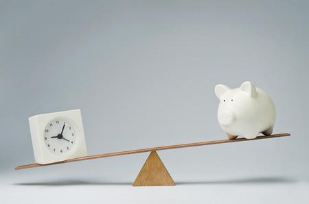 savings risk: Clock and piggy bank balancing on a seesaw