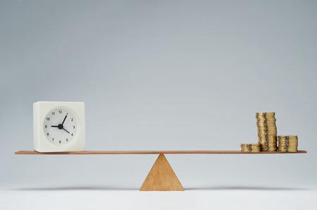 dinero: Reloj y monedas de dinero pila de mantener el equilibrio sobre un balanc�n