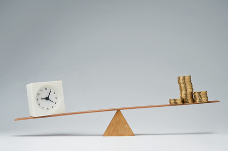 Clock and money coins stack balancing on a seesaw