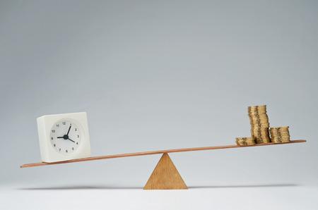 balanza en equilibrio: Reloj y monedas de dinero pila de mantener el equilibrio sobre un balanc�n