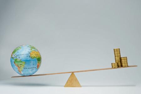 banco mundial: Globo del mundo y monedas de dinero pila de mantener el equilibrio sobre un balanc�n Foto de archivo