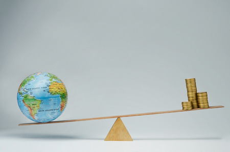 holiday profits: World globe and money coins stack balancing on a seesaw