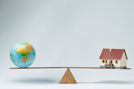real world: World globe and model house balancing on a seesaw Stock Photo