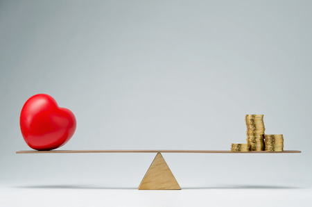 money problems: Red heart shape and money coins stack balancing on a seesaw