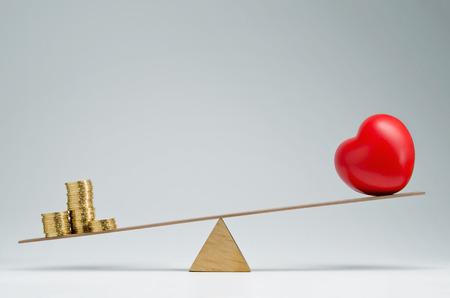 balanza en equilibrio: La forma del corazón rojo y monedas de dinero Pila de equilibrio en un sube y baja