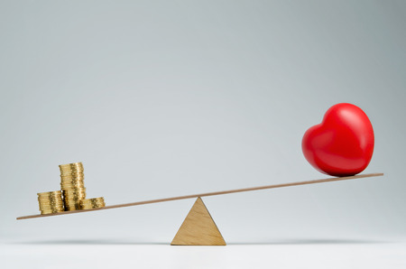 seesaw: Red heart shape and money coins stack balancing on a seesaw