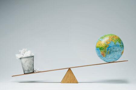 wastepaper basket: Globe balancing on seesaw over wastepaper basket