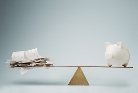 personal finance: Piggy bank balancing on seesaw over a stack of bills