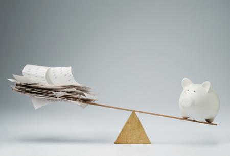 Spaarvarken balanceren op de wip over een stapel facturen Stockfoto