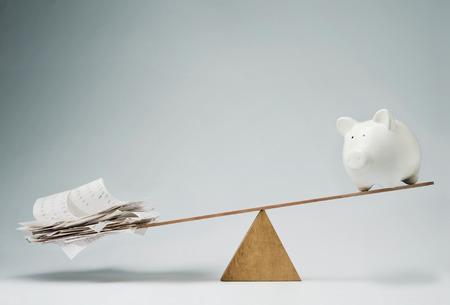balanza: Hucha de equilibrio en el balanc�n sobre una pila de billetes Foto de archivo
