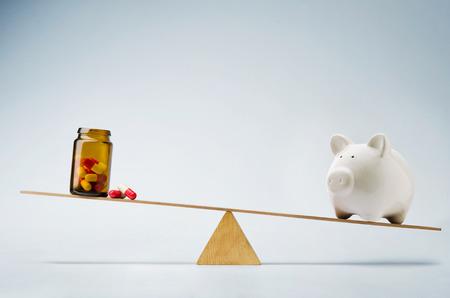 Piggy bank balancing on seesaw over a bottle of pills Фото со стока