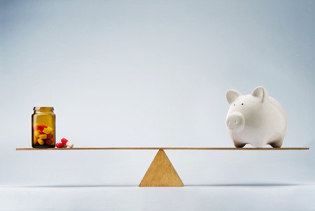 Piggy bank balancing on seesaw over a bottle of pills Stock Photo