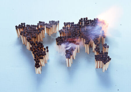 Burning world map made up of matches  photo