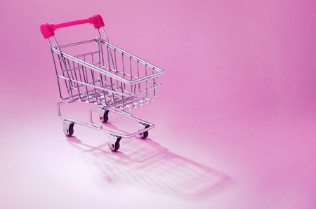 A shopping cart on pink background photo