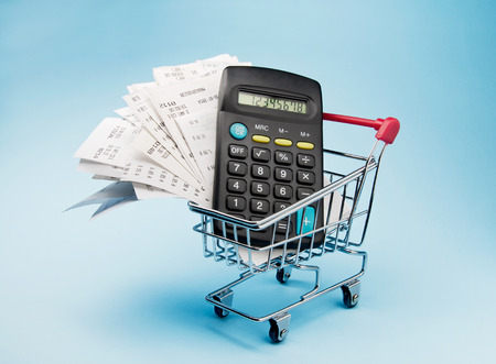 Shopping money. Receipt and calculator in shopping trolley photo