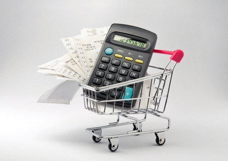 inflation basket: Shopping money. Receipt and calculator in shopping trolley