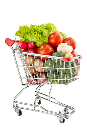 consumable: Shopping trolley full of fresh vegetables isolated on a white background
