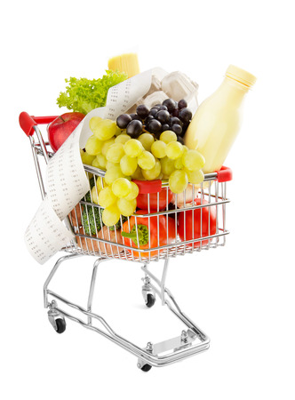 total loss: Shopping trolley full of fresh groceries isolated on a white background