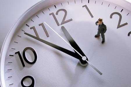 punctual: Empresario figurilla de pie sobre un enorme reloj Foto de archivo