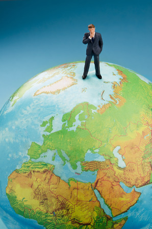 Businessman standing on top of world globe photo