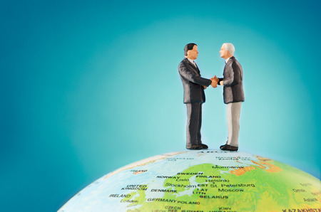 top of the world: Two businessman shaking hands on top of the world