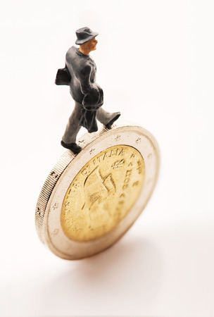 Figurine walking on one euro coin photo