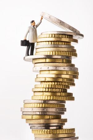Business success. Figure holding up euro coin Фото со стока