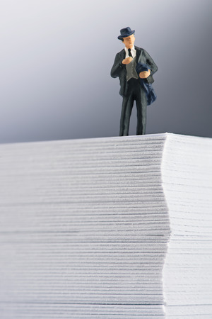 Businessman standing on top of office paper Stock Photo