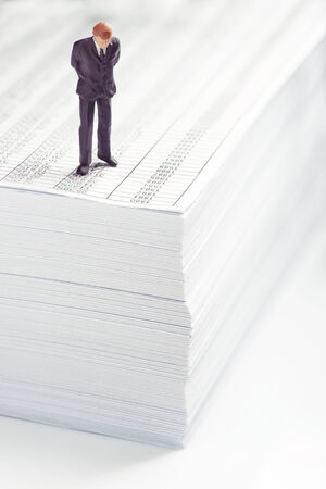 pressured: Businessman standing on top of office paper Stock Photo