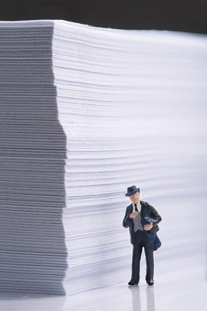Businessman standing beside an office paper  stack