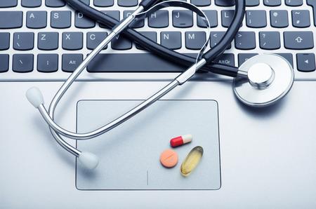 advising: Stethoscope and medicine on laptop computer Stock Photo