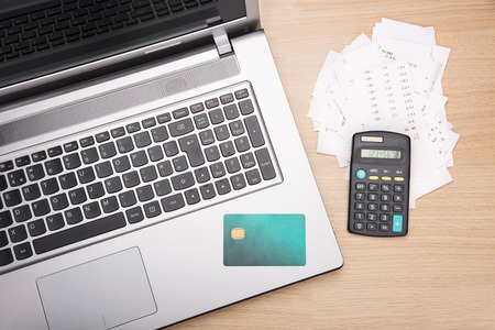 Home finance scene with calculator, laptop and bills photo