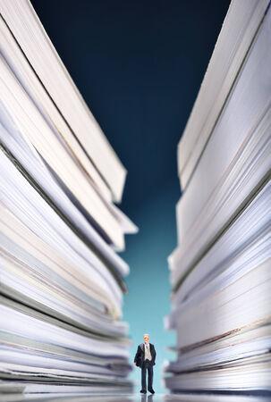 oficina desordenada: Empresario en miniatura se perdió en una enorme pila de papeles