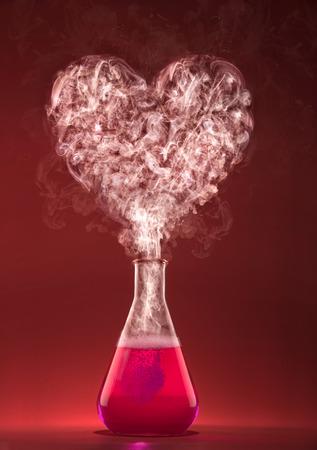 pocion: El amor de la química. Experimento de la ciencia con el humo forma de corazón. Foto de archivo