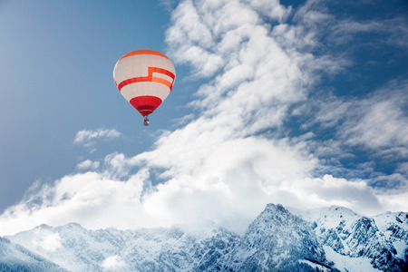 ballooning: Colorful hot-air balloon flying over snowcapped mountain Stock Photo