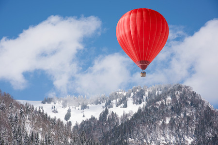 Colorful hot-air balloon flying over snowcapped mountain Stockfoto