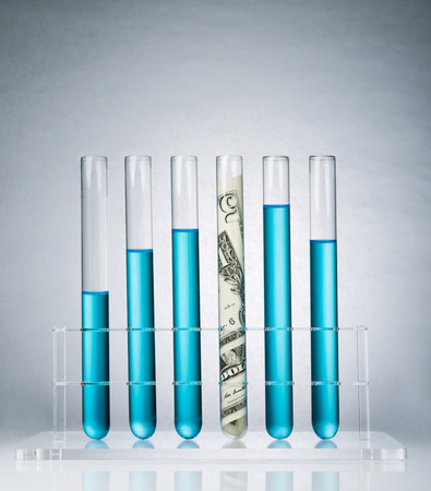Rolled up US paper banknote in a test tube rack representing the costs of medical research