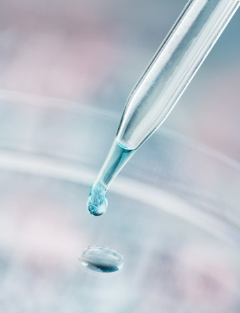 Pipette dispensing a fluid containing a reflection of a DNA sequence gel