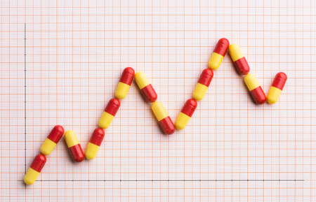 Rising cost of prescription drugs over graph paper Banque d'images