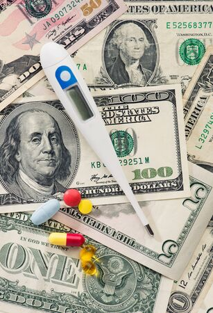 healthcare costs: Healthcare costs. Hundred dollar bills with pills and a thermometer Stock Photo