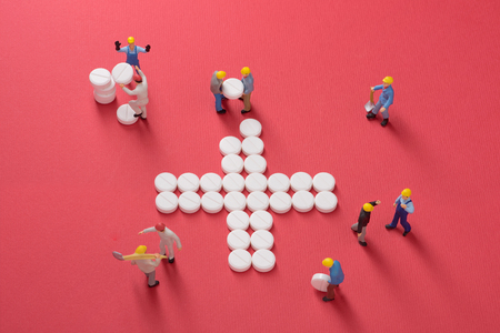 social work aged care: Healthcare system growth. Working men building a cross made of pills, symbol for medical services Stock Photo