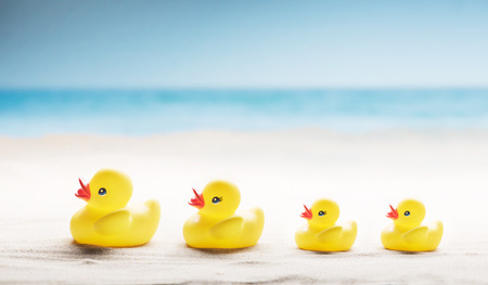 Family holiday concept with rubber ducks walking on the beach